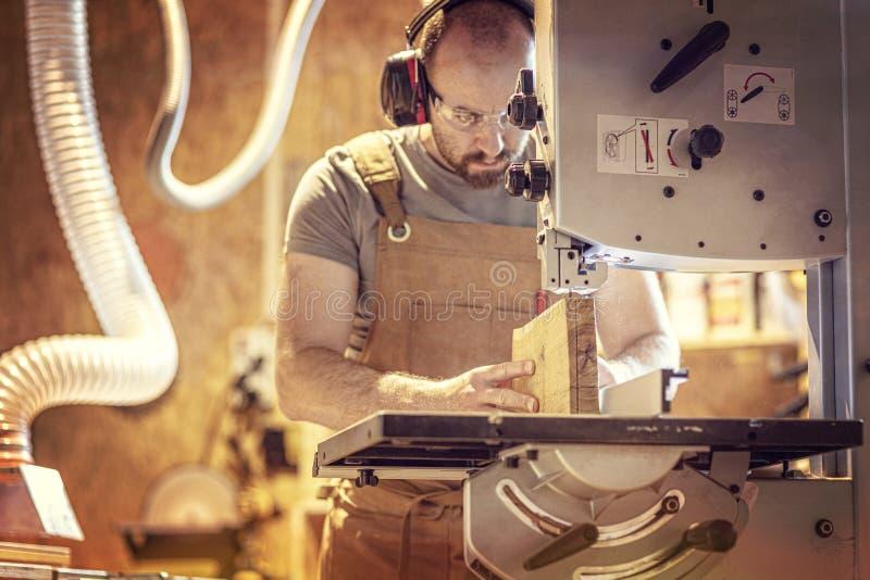 Le portrait d'un charpentier à l'intérieur de son atelier de menuiserie utilisant une bande a vu images stock
