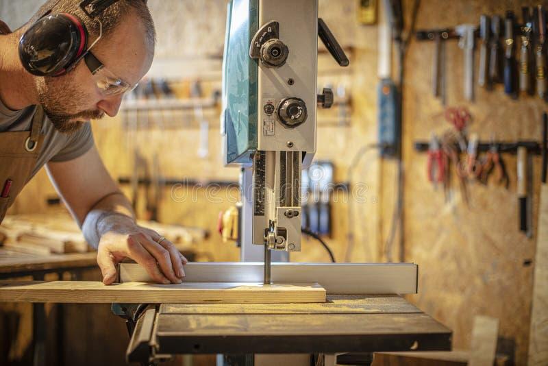 Le portrait d'un charpentier à l'intérieur de son atelier de menuiserie utilisant une bande a vu photo stock