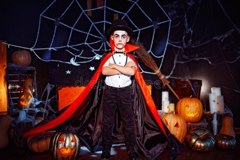 Le portrait d'un garçon s'est habillé dans un costume d'un vampire au-dessus de fond grunge image stock
