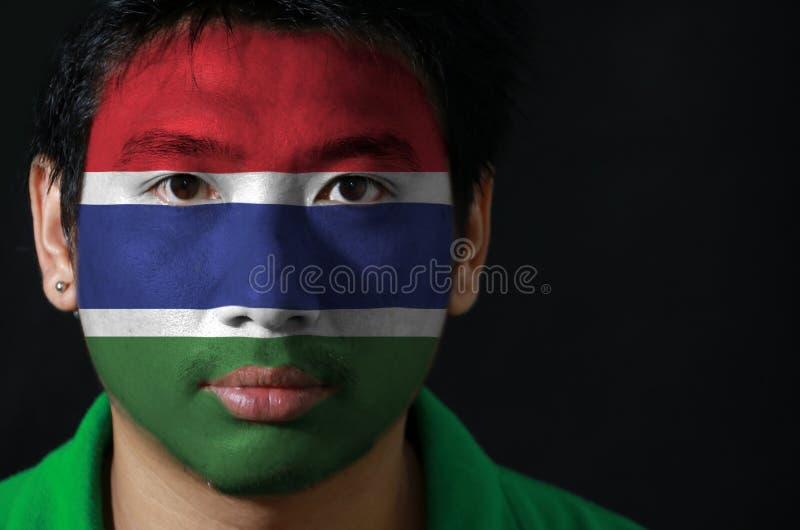 Le portrait d'un homme avec le drapeau de la Gambie a peint sur son visage sur le fond noir images stock