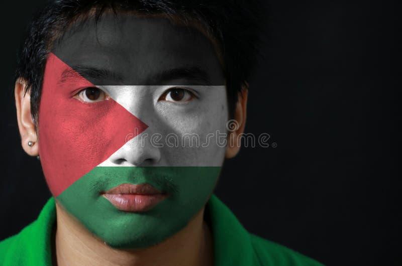 Le portrait d'un homme avec le drapeau de la Palestine a peint sur son visage sur le fond noir image stock