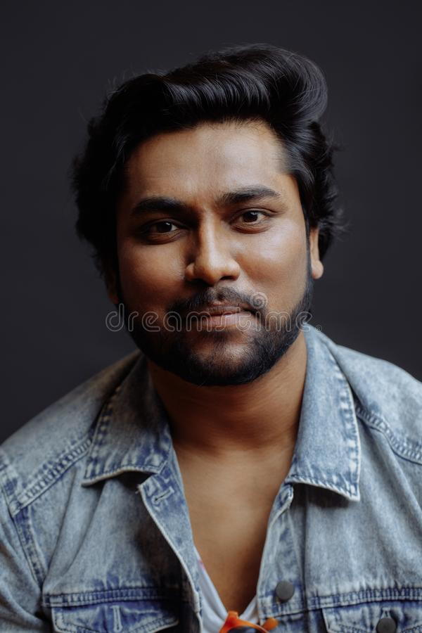 Le portrait d'un homme indien magnifique s'est habillé dans la veste de denim d'isolement image libre de droits