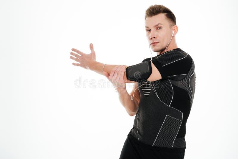 Le portrait d'un jeune a concentré le sportif étirant des mains avant séance d'entraînement photos libres de droits