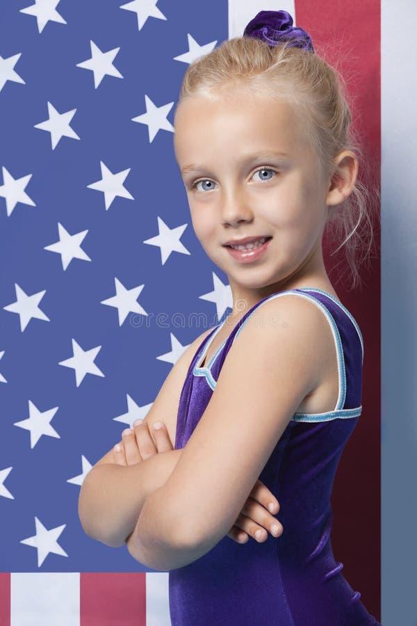 Le portrait d'un jeune gymnaste féminin heureux avec des bras a croisé la position devant le drapeau américain photos stock