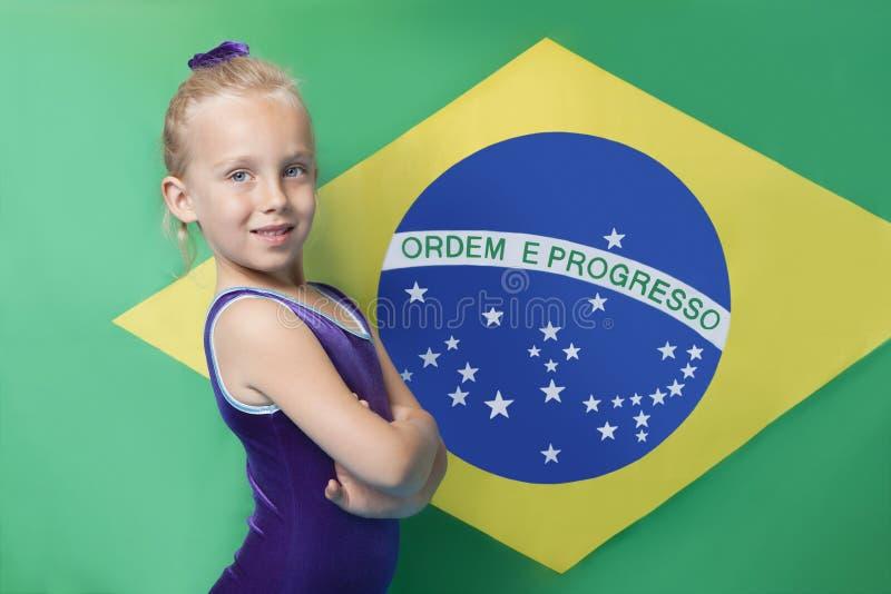 Le portrait d'un jeune gymnaste féminin heureux avec des bras a croisé la position devant le drapeau sud-américain photographie stock