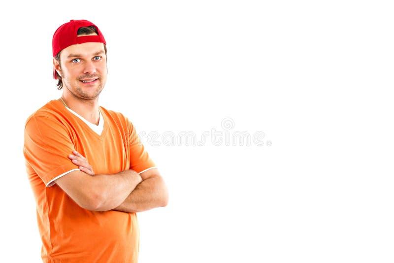 Le portrait d'un jeune homme avec des bras a croisé utiliser un chapeau rouge image libre de droits