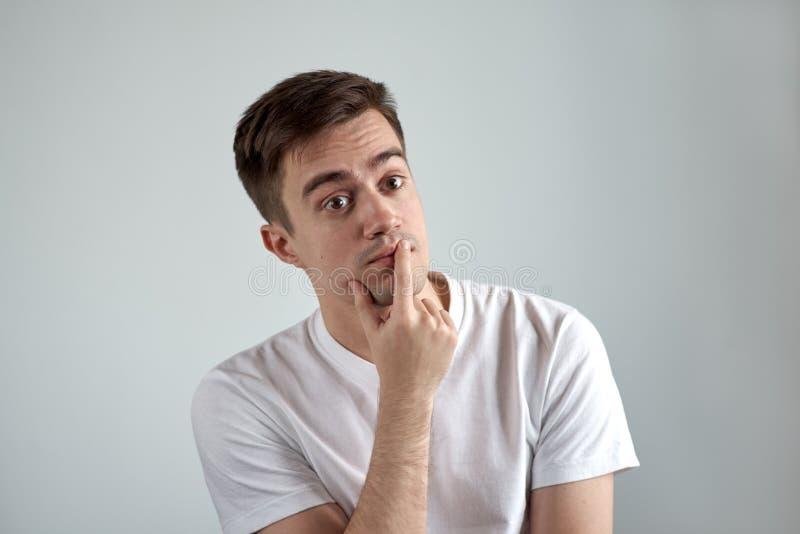 Le portrait d'un jeune homme s'est habillé dans un T-shirt blanc au Th songeur photos libres de droits