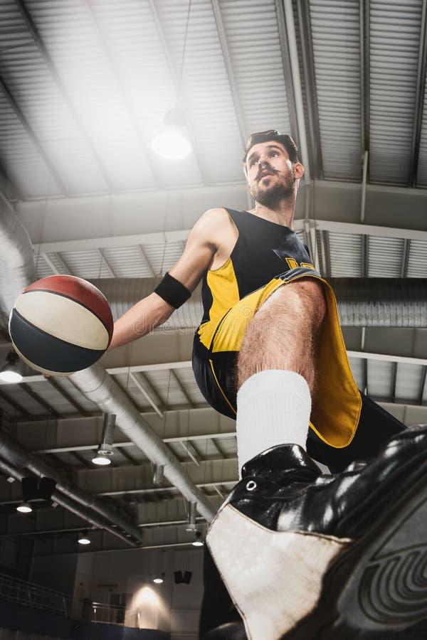 Le portrait d'un joueur de basket avec la boule sur le fond gris de gymnase image stock