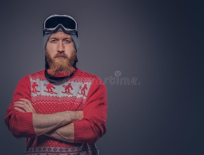 Le portrait d'un mâle barbu roux brutal dans un chapeau d'hiver avec les verres protecteurs s'est habillé dans un chandail rouge, photographie stock