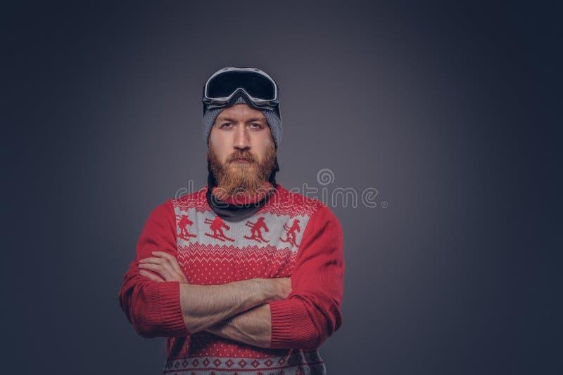 Le portrait d'un mâle barbu roux brutal dans un chapeau d'hiver avec les verres protecteurs s'est habillé dans un chandail rouge, images libres de droits