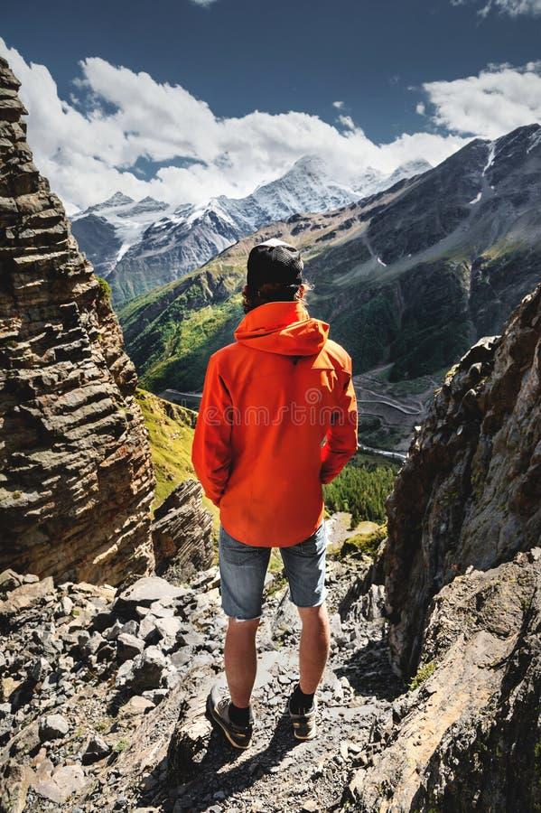 Le portrait d'un randonneur masculin en bref et d'un chapeau du dos se tient sur de hautes roches au bord d'une falaise contre photo libre de droits