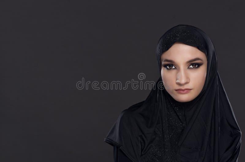 Le portrait d'une belle femme musulmane s'est habillé dans le hijab noir photos libres de droits