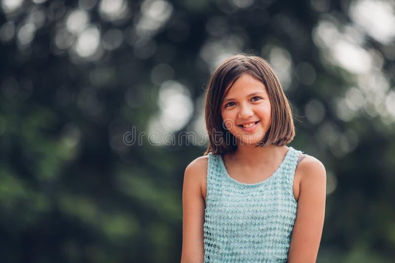 Le portrait d'une belle fille dans le bokeh des feuilles est un vert images stock