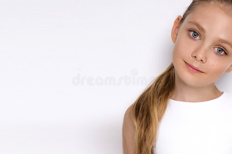 Le portrait d'une belle fille de petite fille dans de longs cheveux blonds et le blanc s'habillent images stock