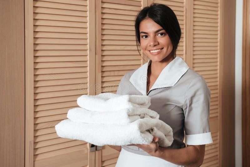 Le portrait d'une domestique d'hôtel jugeant fraîche nettoient les serviettes pliées image libre de droits