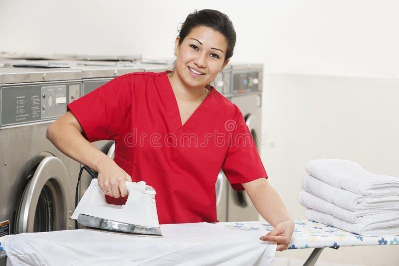 Le portrait d'une employée heureuse dans repasser uniforme rouge vêtx de la laverie automatique image libre de droits