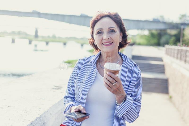 Le portrait d'une femme élégante attirante mûre s'est retiré avec une tasse photographie stock libre de droits