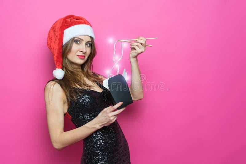 Le portrait d'une femme riante gaie de brune dans le chapeau de No?l et la robe noire exquise tient dans sa main une bo?te de pap image libre de droits