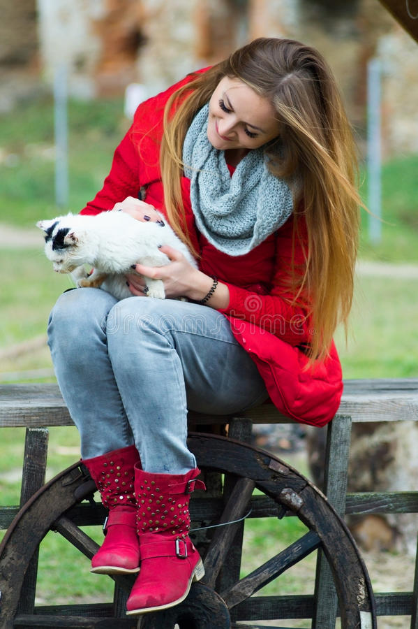 Le portrait d'une femme s'est habillé en rouge avec un chat dans des ses bras photo stock