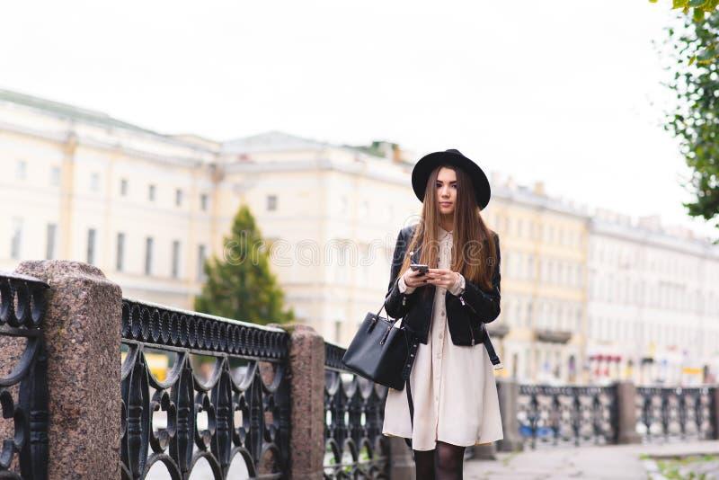 Le portrait d'une fille élégante de hippie s'est habillé dans des vêtements frais posant sur la rue tandis que téléphone de cellu photographie stock