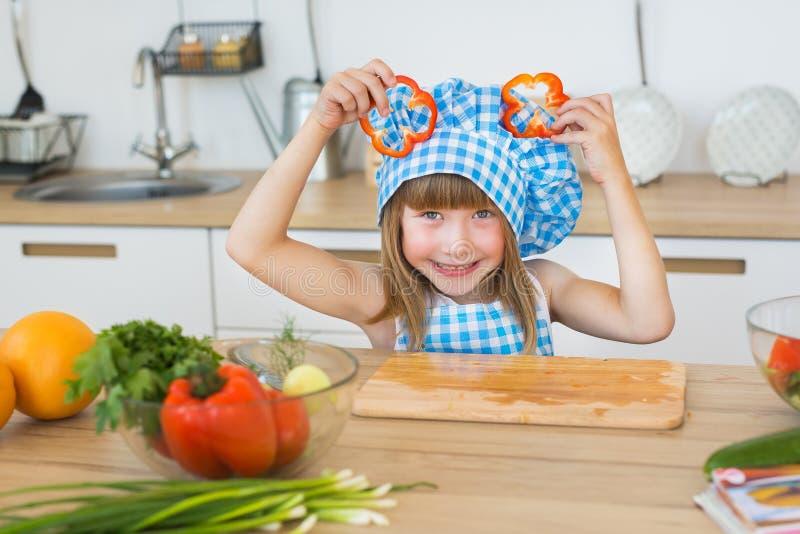 Le portrait d'une fille assez petite dans le cuisinier vêtx avec des tranches d'un paprika sur une tête photo libre de droits