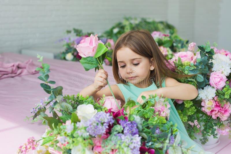 Le portrait d'une fille assez petite dans une robe de turquoise place des fleurs dans un studio image libre de droits