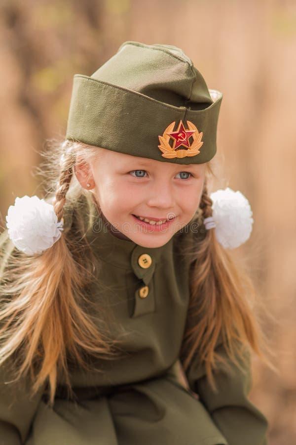 Le portrait d'une fille avec deux tresses et blancs cintre dans l'uniforme sur Victory Day photo stock