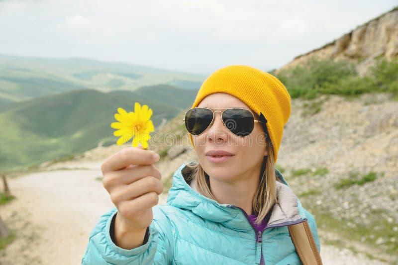 Le portrait d'une fille dans un chapeau et des lunettes de soleil tient une fleur en premier ressort sur la nature Le concept de  photo stock