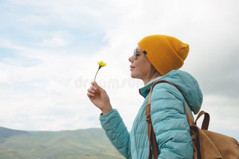 Le portrait d'une fille dans un chapeau et des lunettes de soleil tient une fleur en premier ressort sur la nature Le concept de  image libre de droits