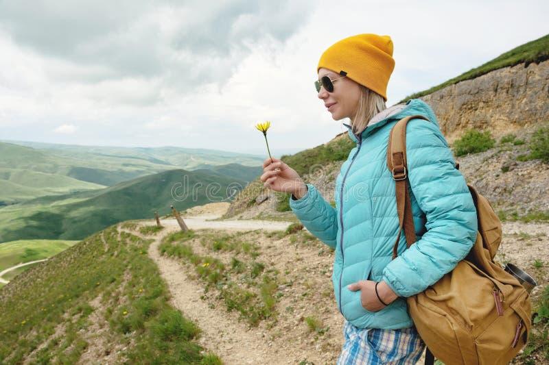 Le portrait d'une fille dans un chapeau et des lunettes de soleil tient une fleur en premier ressort sur la nature Le concept de  images libres de droits