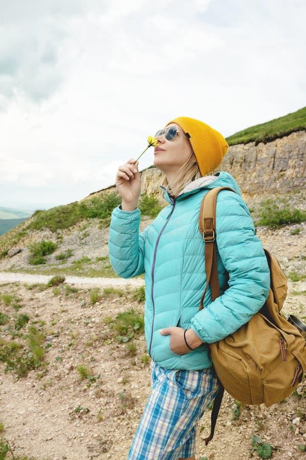 Le portrait d'une fille dans un chapeau et des lunettes de soleil tient une fleur en premier ressort sur la nature Le concept de  images stock