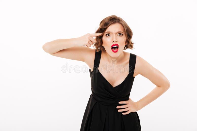 Le portrait d'une fille fâchée s'est habillé dans la robe noire image stock