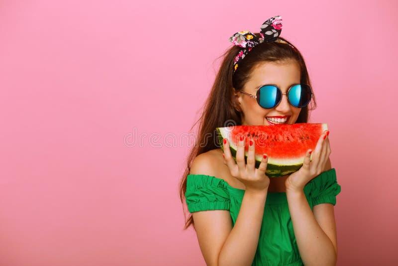 Le portrait d'une fille heureuse, tenant une tranche de pastèque essayent à disposition de mordre, au-dessus du fond rose coloré  images stock