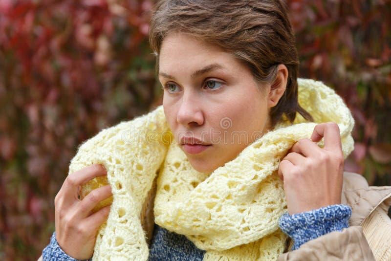 Le portrait d'une fille qui redresse un blanc a tricoté l'écharpe photographie stock