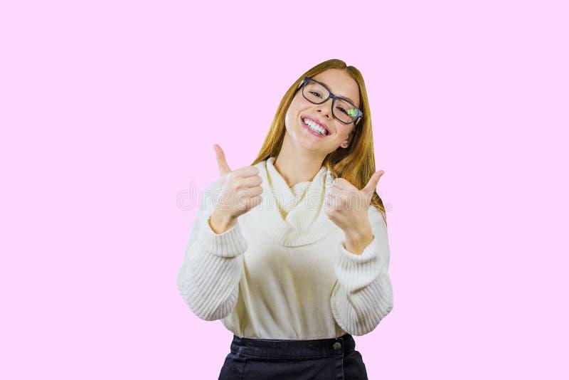 Le portrait d'une fille rousse dans les verres et un chandail blanc montre la classe avec les deux mains et sourires avec sa tête images libres de droits