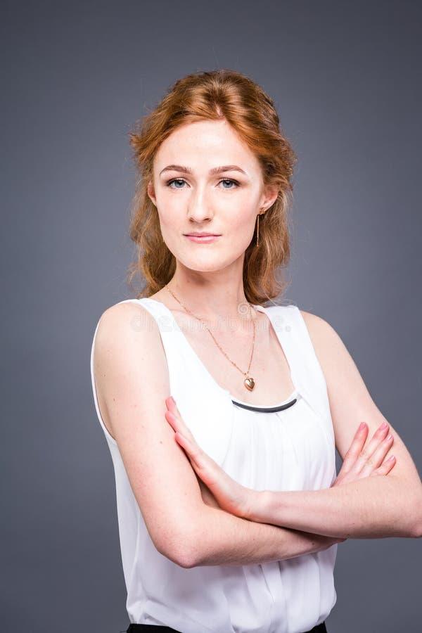Le portrait d'une jeune belle fille redhaired dans le studio sur un gris a isolé le fond Une femme se tient avec ses bras pliés photographie stock libre de droits