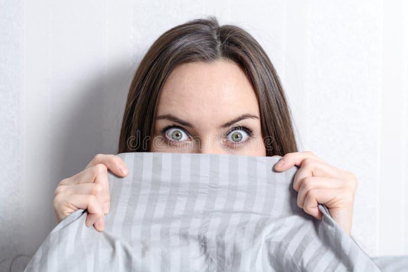 Le portrait d'une jeune brune avec se demander observe la dissimulation derrière un plan rapproché couvrant gris photographie stock
