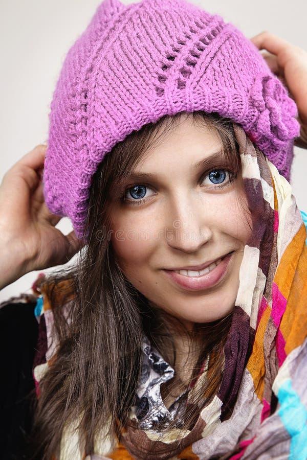 Le portrait d'une jeune femme caucasienne avec un pourpre a tricoté le chapeau image libre de droits