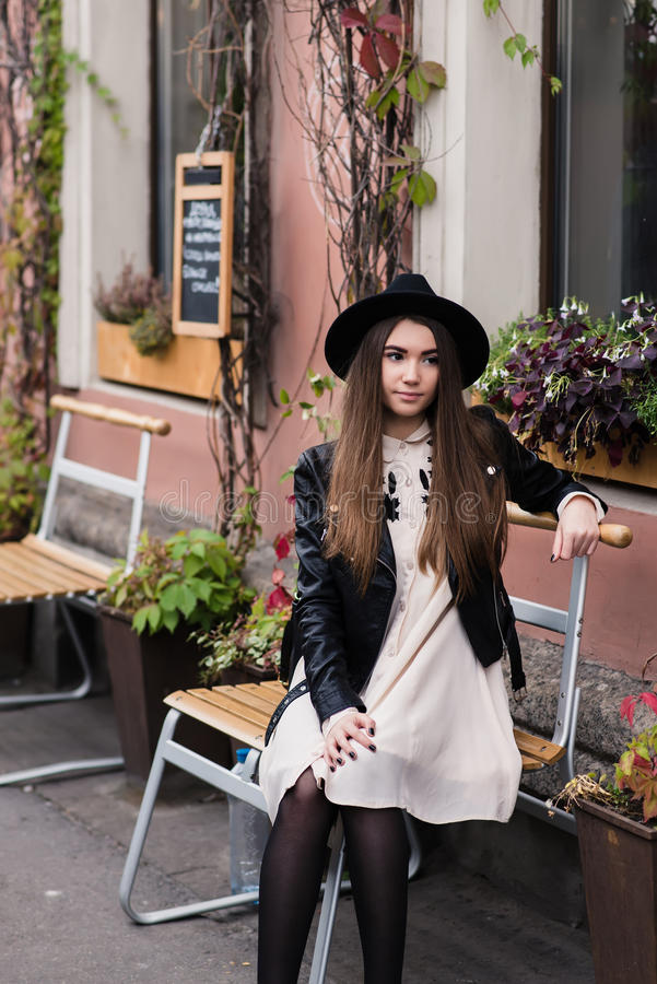 Le portrait d'une jeune femme s'est habillé dans des vêtements à la mode frais se reposant sur une chaise de rue près du bâtiment photographie stock libre de droits