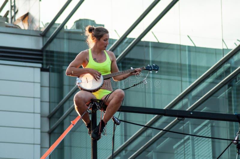 Le portrait d'une jeune femme tout bien pesé avec le banjo pour des acrobaties aériennes extérieures montrent à Mulhouse photographie stock libre de droits