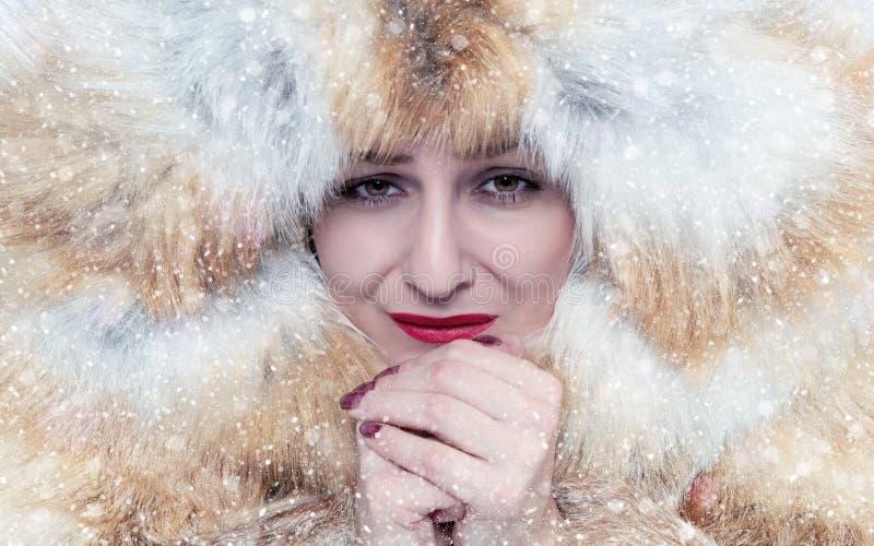 Le portrait d'une jeune fille congelée dans un manteau de fourrure de renard, chauffent ses mains, froid, neige, gel, tempête de  photo stock