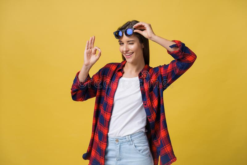 Le portrait d'une jeune fille heureuse en été vêtx montrer le geste correct au-dessus du fond jaune image libre de droits