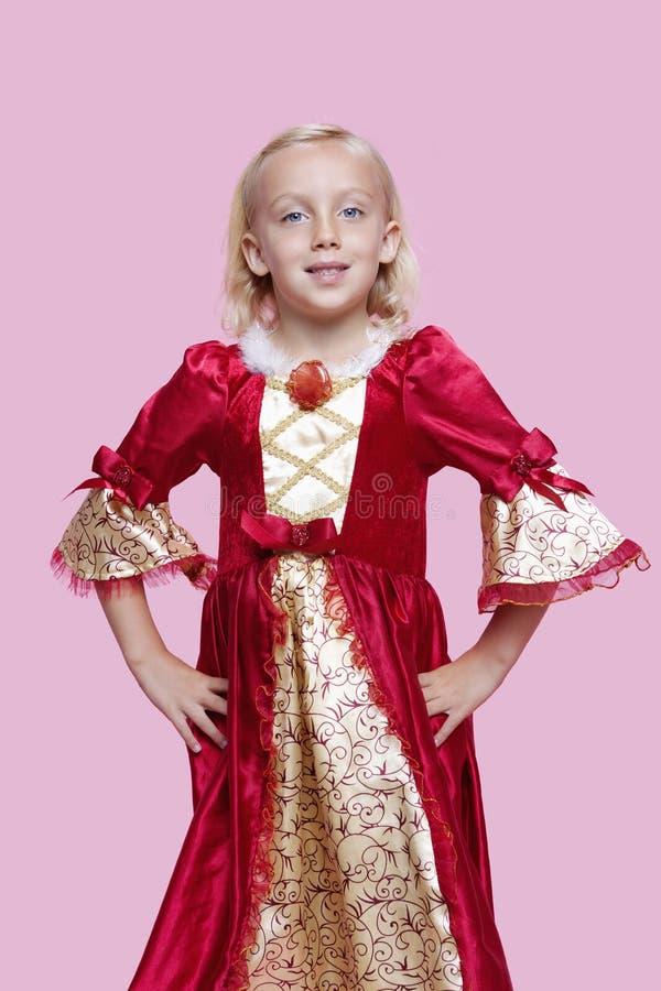 Le portrait d'une jeune fille heureuse s'est habillé dans le costume de princesse au-dessus du fond rose image stock