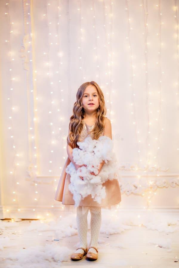 Le portrait d'une petite fille avec les cheveux bouclés le réveillon de Noël, la nouvelle année apportera des cadeaux images stock
