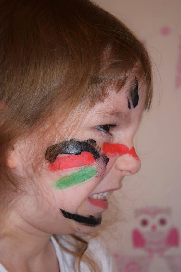 Le portrait d'une petite fille avec un visage peint aiment un guerrier Photo de profil photographie stock