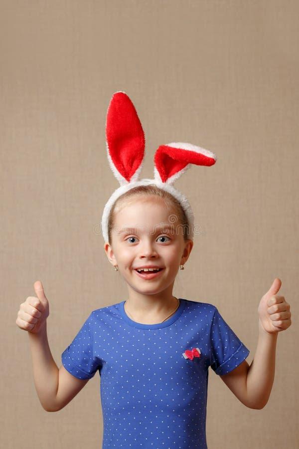 Le portrait d'une petite fille mignonne s'est habillé dans des oreilles de lapin de Pâques que les expositions font des gestes pa image libre de droits