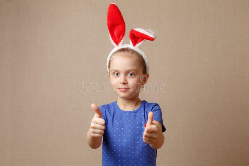 Le portrait d'une petite fille mignonne s'est habillé dans des oreilles de lapin de Pâques que les expositions font des gestes pa image stock