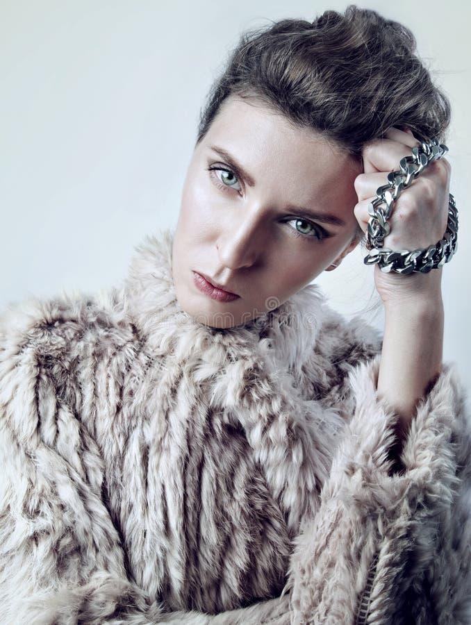 Le portrait de beauté d'une jeune femme blanche en fourrure avec la chaîne, semblent strict à l'appareil-photo photos stock