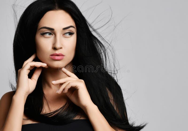 Le portrait de concept de publicité de la brune de femme avec des cheveux flottant dans le vent touche son menton avec le dos de  photographie stock