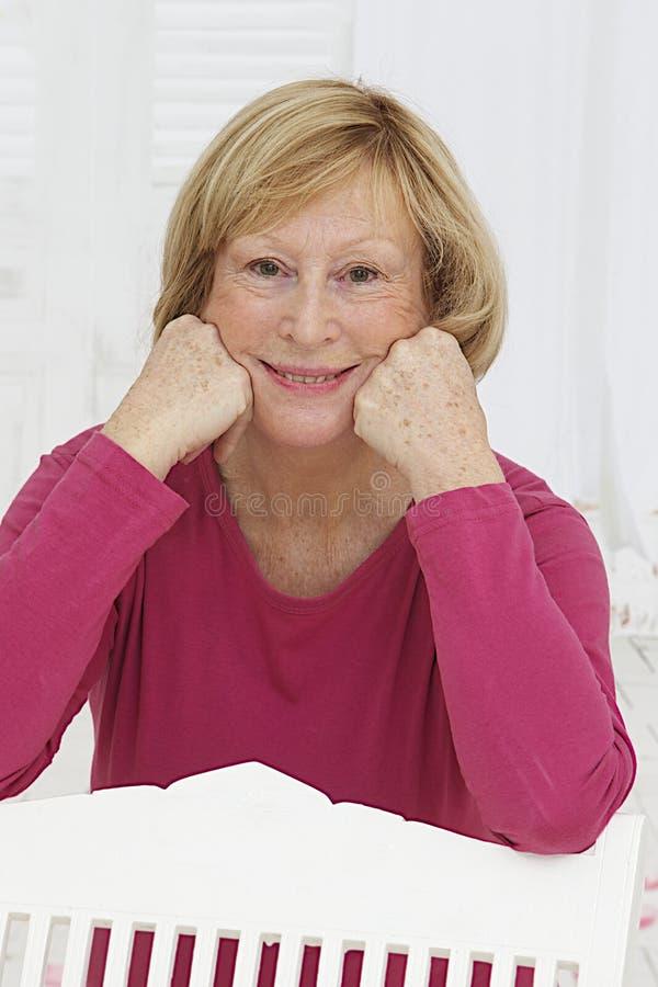 Le portrait de détendent la femme supérieure s'asseyant dehors image libre de droits